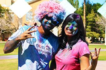 Two students covered with purple and blue paint, posing the ASU pitchfork
